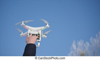 Drone with a video camera in the hands of men against the sky Drone with camera in man hand