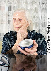 Senior woman applying face cream at home