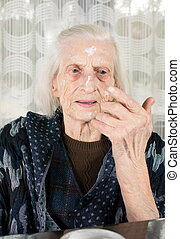 Senior woman applying face cream at home