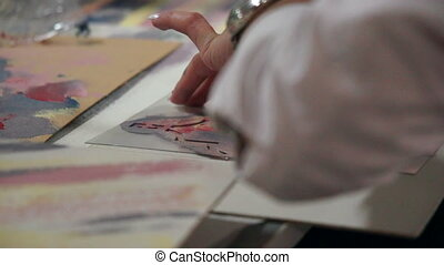 Hands of professional artist decorate paper using paint and...