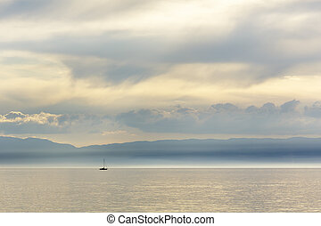 Sailboats on the lake is seen in the far distance -...