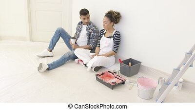 Young couple taking a break from renovating - Young couple...
