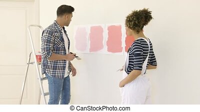 Young couple debating a new paint color for the wall of...