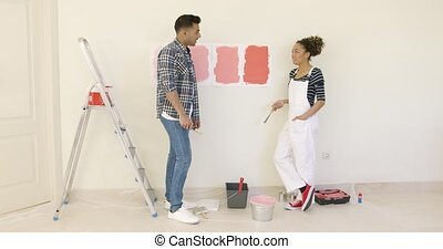 Young couple trying to decide on a paint color for the...