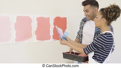 Young couple checking paint swatches on cards against...