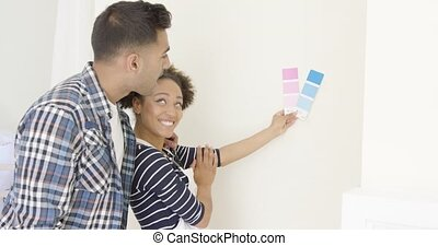 Young couple choosing a paint color for the wall in their...