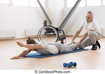 Helpful physical therapist stretching the handicapped in the gym