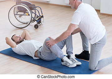 Aged general practitioner stretching the handicapped in the sports hall