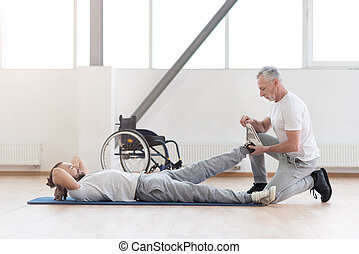 Concentrated aged orthopedist helping with disabled patient