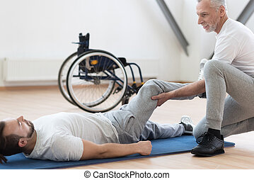 Charismatic orthopedist stretching the handicapped in the gym