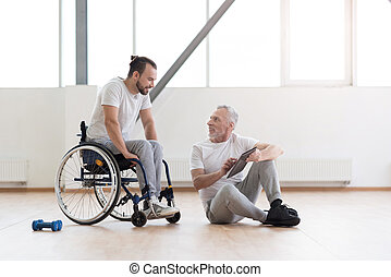 Cheerful orthopedist communicating with disabled patient in the gym