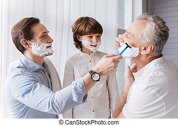 Nice handsome man helping his father to shave - Do you need...