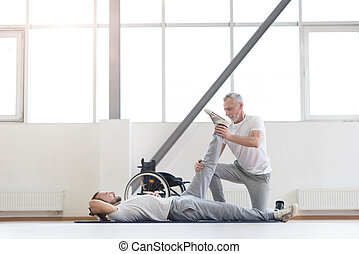 Cheerful aged orthopedist working out with disabled patient