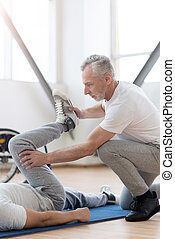 Powerful orthopedist stretching the handicapped in the gym