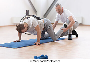 Aged physical therapist stretching the handicapped in the gym