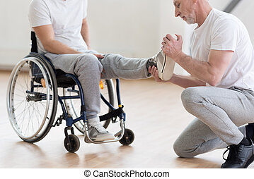 Aged orthopedist working with handicapped in the gym