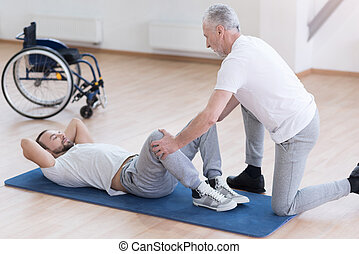 Helpful general practitioner stretching the handicapped in the sports hall