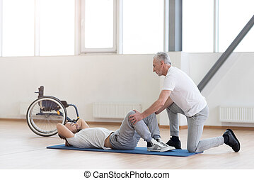 Kindly general practitioner stretching the handicapped in the gym