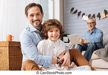 Positive pleasant man hugging his son - Happy family....