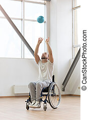 Delighted young handicapped throwing up the ball in the gym...