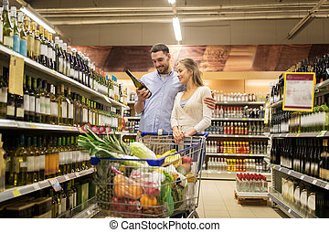 couple with wine and shopping cart at liquor store - sale,...