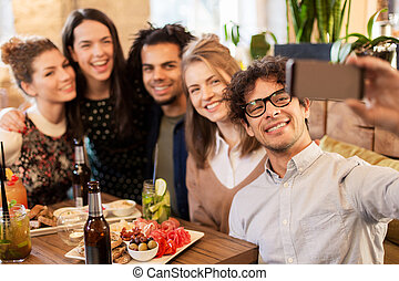 friends taking selfie by smartphone at bar or cafe -...