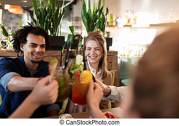 happy friends clinking drinks at restaurant - leisure,...