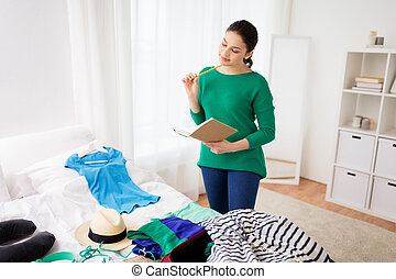 woman with notebook planning her trip at home - tourism,...