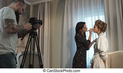 The videographer shoots make-up processes - the videographer...