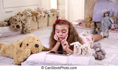 Little girl using touchpad - Cute little girl lying on the...