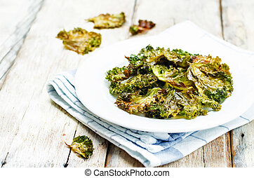 Kale chips on wood background. toning. selective focus