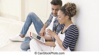 Handsome black couple sits and uses tablet while seated on...