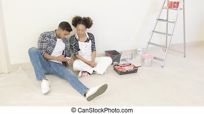 Black couple relaxes after long day of painting and take...