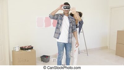 Man using virtual reality glasses gets help from wife who...