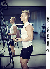 Handsome blond young man exercising triceps on gym equipment