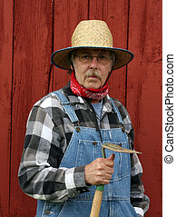 farmer portrait with barn background - farmer holding a...