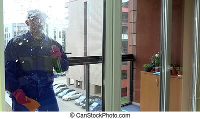 a professional window cleaner soaps and squeegees a window...