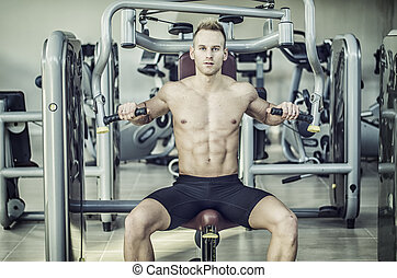 Handsome young man in gym exercising pecs on machine