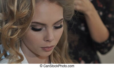 Bride preparing for the wedding. Hair Styling. The bride's...