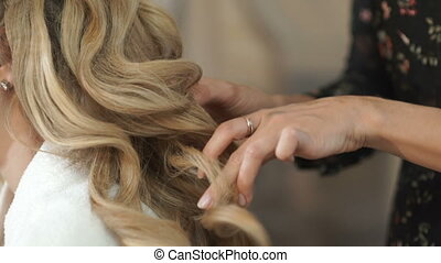 The procedure of hair extensions - Hairdresser straightens...