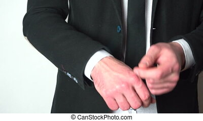 Businessman adjusting sleeve cuffs of his shirt, closeup,...