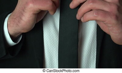 Businessman adjusting his tie at home, slow motion, closeup
