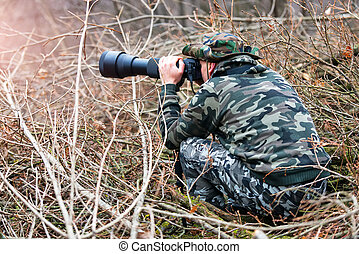 Photo hunting camouflaged in the branches  in the woods