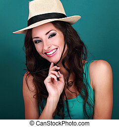 Natural expression smiling beautiful woman in straw summer hat with long curly hair style looking on light green background. Closeup bright portrait