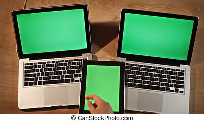 Top view man scrolling images,digital tablet lying on two laptops vertical