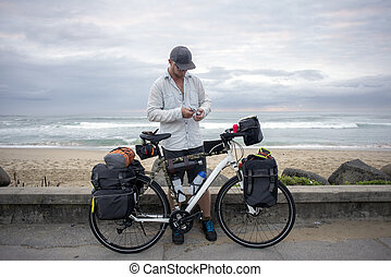 Long Distance Cyclist with Bicycle by Ocean - A long...