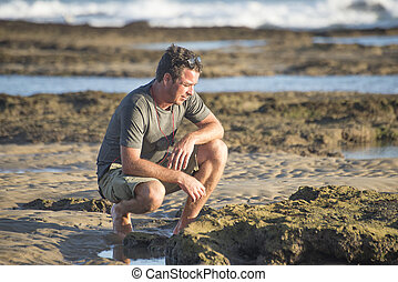 Man on rocks by ocean - A middle aged man sits on his...
