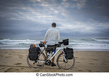 Long Distance Cyclist on beach with Bicycle - A long...