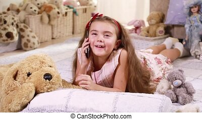 Child chatting on phone - A little Caucasian girl lying on...
