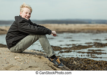 Smiling teen with arms around knees outside - Side view on...